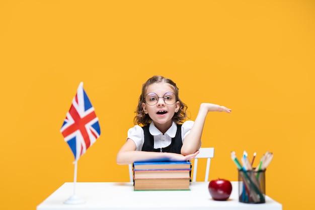 Эмоциональная кавказская школьница сидит за партой и поднимает руку на уроке английского флага великобритании
