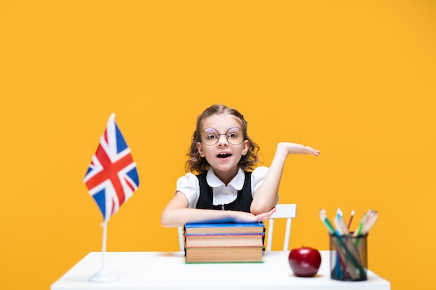 Emotional caucasian schoolgirl sits at the desk and raises hand english lesson great britain flag