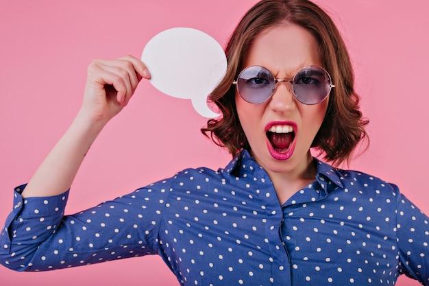 不安を表現する青いシャツを着た感情的な白人女性。ピンクの壁に分離された巻き毛の少女の叫び。