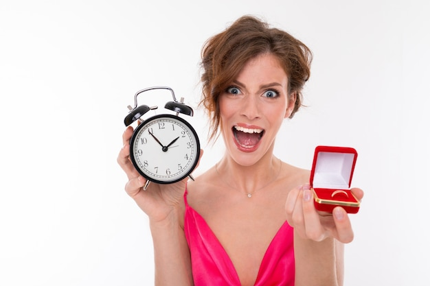 Emotional charming girl in a pink dress with a neckline holds a red box with a wedding ring and an alarm clock on a white wall