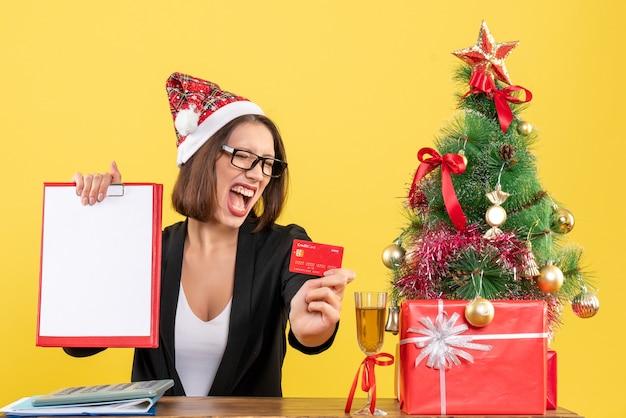 黄色の孤立したオフィスで銀行カードと文書を示すサンタクロースの帽子と眼鏡とスーツの感情的な魅力的な女性