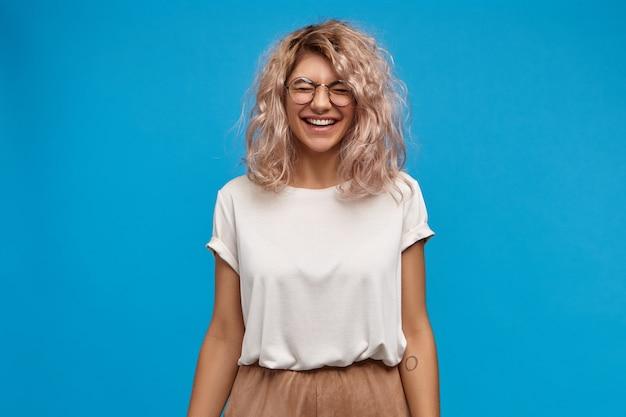 トレンディなメガネをかけた、感情的に魅力的な若いヨーロッパ人女性が、笑い、目を閉じ、大きく笑って、白い完璧な歯を見せています。楽しんで気分の良い魅力的な女の子