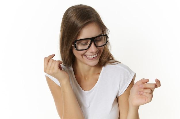 Emotiva affascinante giovane donna europea che indossa una maglietta bianca e occhiali alla moda che sorride ampiamente e guarda in basso, gesticolando come se ballasse. persone, stile di vita, ottica e visione
