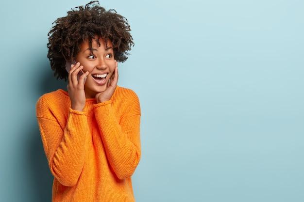 정서적이고 쾌활한 여성이 휴대 전화로 대화하고, 대화 상대와 인상을 공유하고, 현대 기술을 즐기고, 캐주얼 한 옷을 입고, 파란색 벽에 고립 된 상태로 휴대 전화를 통해 친구에게 전화를 겁니다.