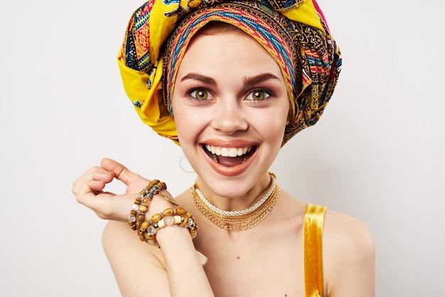 彼女の頭にターバンを持った感情的な陽気な女性伝統的な服のスタジオのクローズアップ。高品質の写真