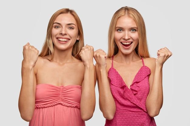 정서적 쾌활한 여성은 행복으로 주먹을 쥐고 좋은 결과를 얻고 기분이 좋습니다.