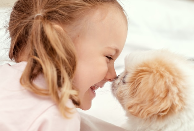 Emotional child and baby dog kid play with puppy on bed at home friendship between animal and child