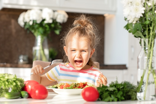 Emotional child enjoy eat healthy salad kitchen fresh vegetables on table meal nutrition and vegan