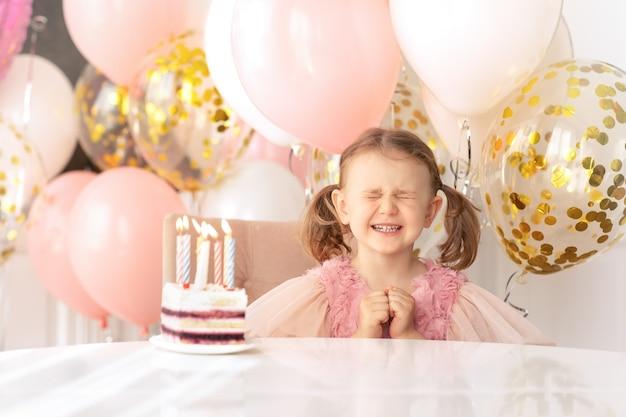 감정적인 어린 소녀는 눈을 감고 생일 케이크에 촛불을 끄기 전에 생일 소원을 빌다