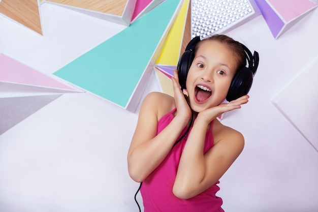 Emotional child girl in headphones listening to music and singing