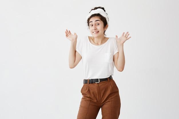 白いtシャツと茶色のズボンを身に着け、肩をすくめて、開いた手のひらで立って、無関心、不確実性、無視または無関心を表現する感情的な無知な若い黒髪の女性。