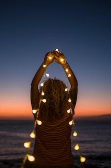 大人の女性と黄色い電球のライトの焦点がぼけた希望と信仰の感情的な概念