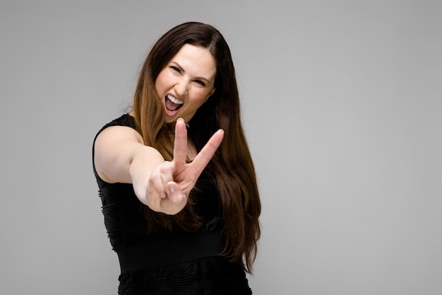 Emotional confident plus size model standing in studio showing peace gesture on gray