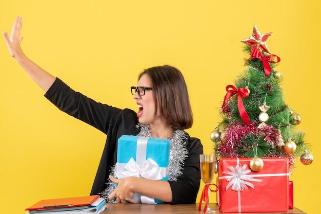 Эмоциональная растерянная бизнес-леди в костюме в очках держит подарок, зовет кого-то и сидит за столом с рождественской елкой в офисе