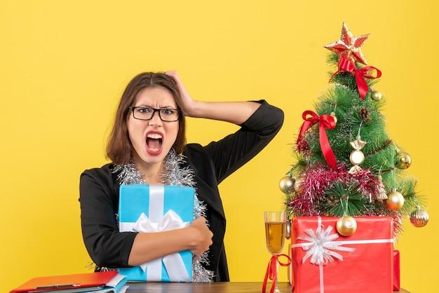 Signora di affari confusa emotiva in vestito con gli occhiali che tiene il suo regalo e che si siede a un tavolo con un albero di natale su di esso in ufficio