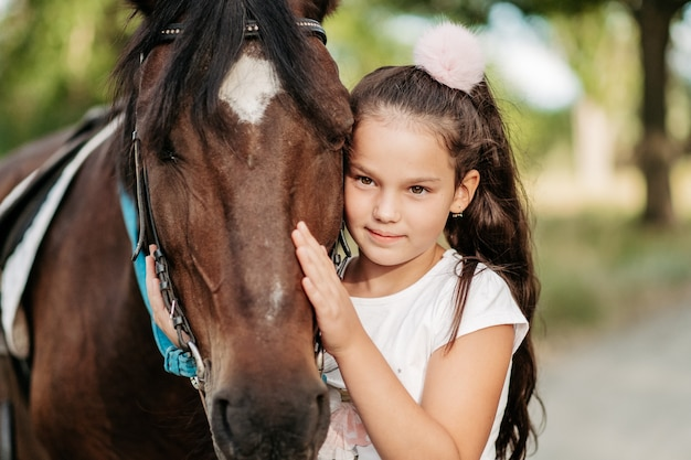Emotional contact with the horse. the girl rides a horse in the summer.