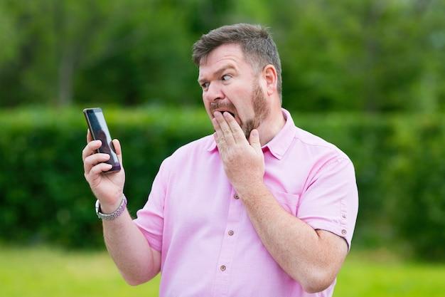 モバイルスマートフォンでの男性の感情的な会話不信と怒りの大人の男性