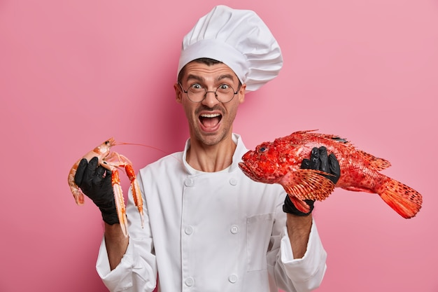 Emotional cook poses with seafood in white uniform, screams loudly, invites visiting his restaurant