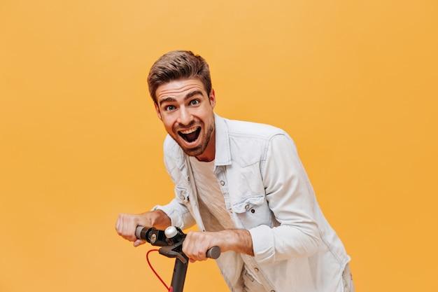 トレンディなシャツと白いtシャツに生姜のひげを生やして楽しんで孤立した壁にカメラを覗き込んでいる感情的なクールなスタイリッシュな男