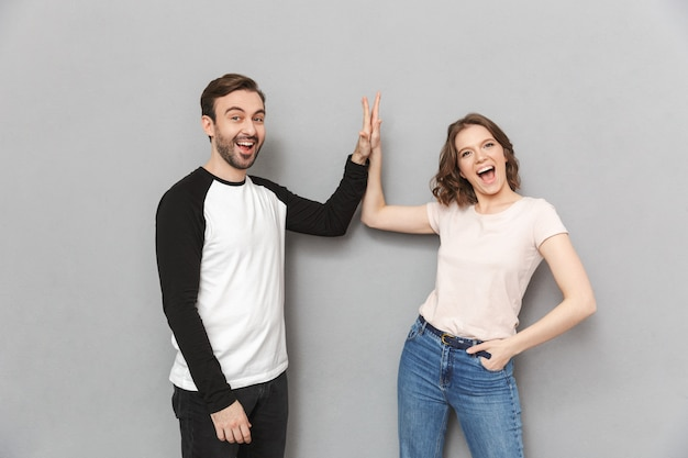 Emotional couple friends gives a high five to each other.
