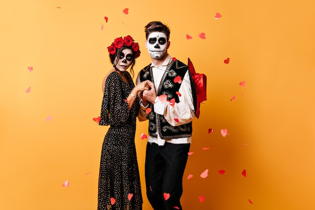 Emotional couple holding hands, posing for portrait surrounded by heart confetti. elegant costumes of guy and girl complement their unusual image for halloween