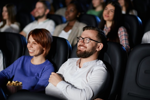 Emotional couple watching comedy in movie theater.