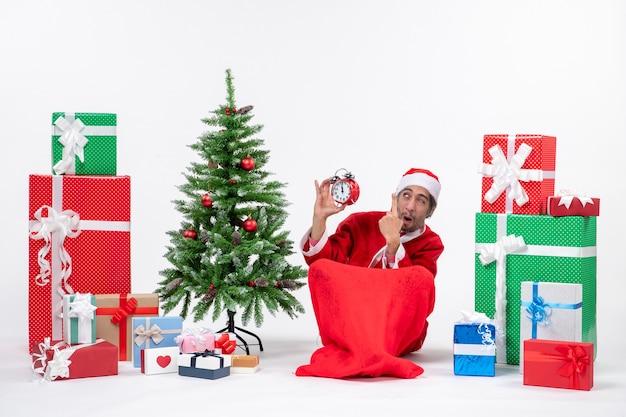 地面に座って、贈り物の近くに時計を表示し、白い背景にクリスマスツリーを飾った感情的な狂気の驚きのサンタクロース