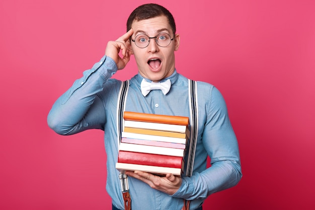 Emotional creative dark haired young man puts forefinger to his temple, holds many books in one hand, opens his mouth and eyes widely, keeping amazing idea in his mind.