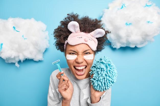 La donna afroamericana riccia emotiva urla ad alta voce indossa la maschera da notte tiene il rasoio e la spugna che vanno a fare la doccia vestita in indumenti da notte pone contro il muro blu