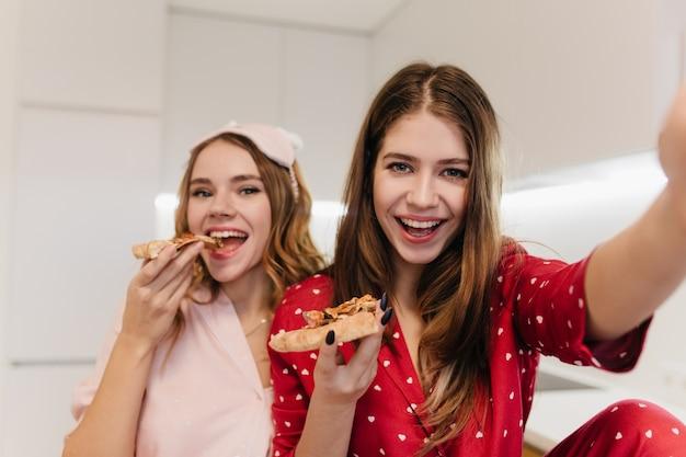 Ragazza riccia emotiva che mangia pizza con il sorriso. foto interna della donna dai capelli castani felice in indumenti da notte rossi che fa selfie con un amico.