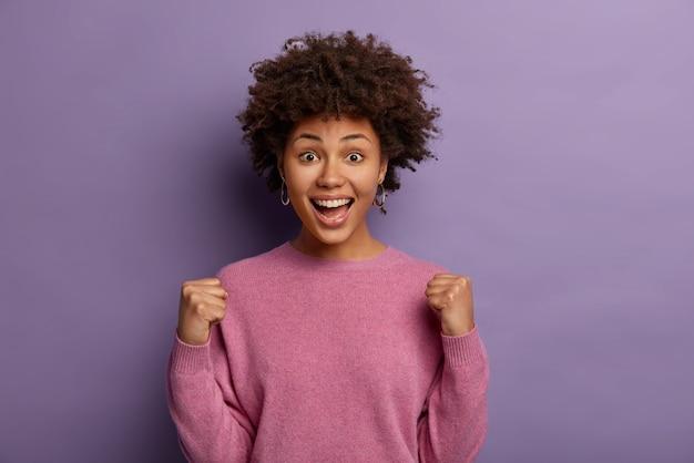 La donna emozionata dai capelli ricci emotiva alza le mani, grida per la squadra preferita mentre guarda la competizione sportiva, sorride positivamente, indossa un maglione casual, isolato sul muro viola. realizzazione