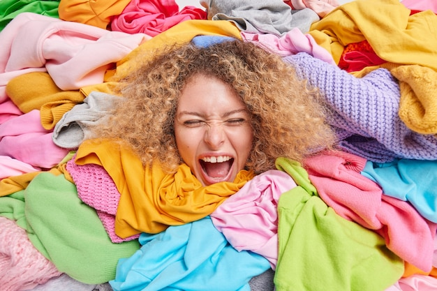 Emotional curly haired female volunteer surounded by big stack of colorful clothes gathered for charity donates to poor people exclaims loudly keeps mouth opened. reuse recycling clothing concept