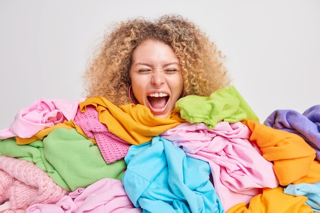 Emotional curly haired woman exclaims loudly keeps mouth opened buried in multicolored clothes collects clothing for recycling does spring cleaning of wardrobe isolated over white