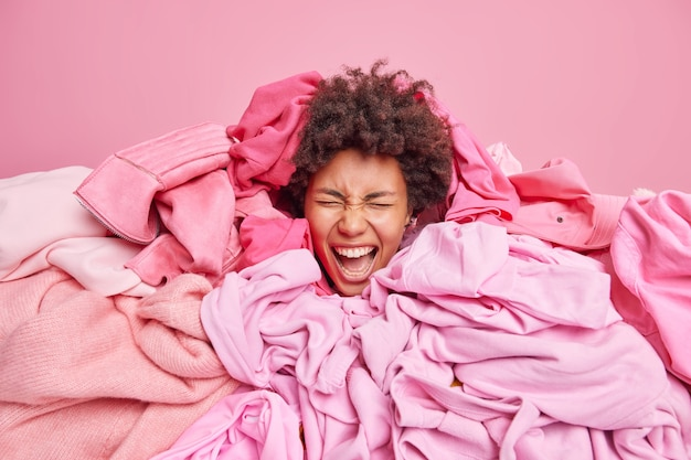 Emotional curly haired woman surrounded by pile of messy clothes from closet exclaims loudly keeps mouth opened has real chaos at home busy doing laundry. everything in pink color. clothing concept
