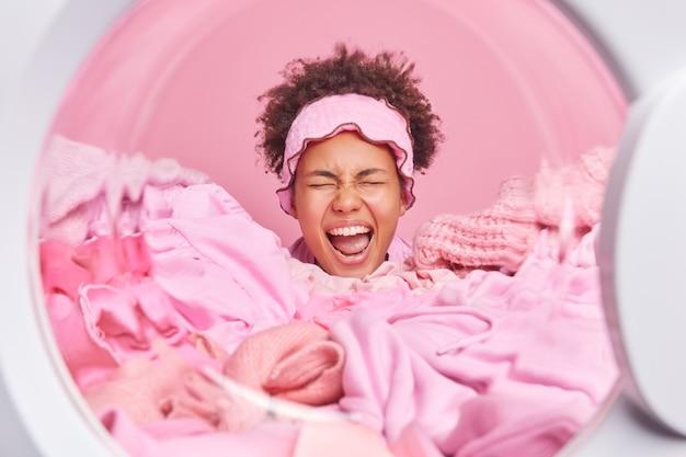 자동 세탁실에서 세탁할 옷으로 덮인 감정적인 곱슬머리 젊은 여성은 분홍색 벽이 집안일을 한다고 긍정적으로 웃는다