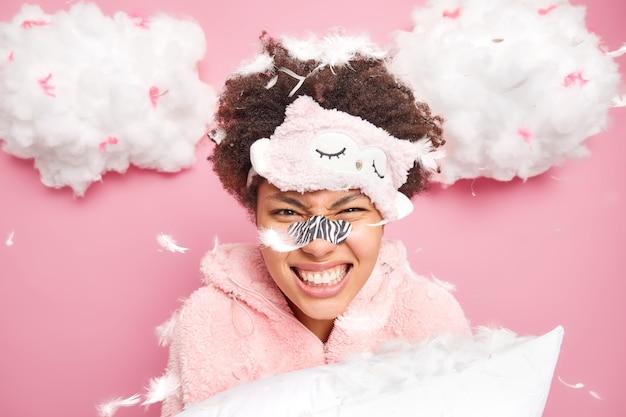 感情的な巻き毛の女性が歯を食いしばって、羽の下で枕投げのポーズが飛び交うと、ピンクの壁に孤立した黒ずみを減らすために、スリープマスクが鼻にパッチを適用します。