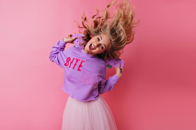 スケートボードで踊る感情的な巻き毛の女性。ピンクで浮気している機嫌の良いヨーロッパの面白い女の子。