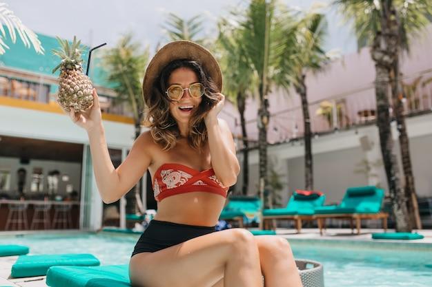プールの近くでパイナップルと笑顔でポーズをとる感情的な巻き毛の女性。夏の週末に天気の良い日を楽しんでいるビキニの華やかな笑いの女性。