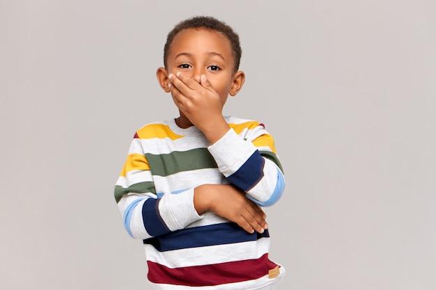 충격이나 비밀의 표시로 손으로 입을 덮고 머리에 여전히 혀를 유지하면서 놀람이나 놀람을 표현하는 감정적 인 귀여운 아프리카 계 미국인 소년. 진정한 인간의 감정과 반응