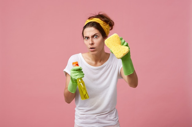Emotional cute female posing in green rubber gloves, equipped with yellow sponge and spray detergent, ready for tidying up and cleaning house, looking with funny expression on her face