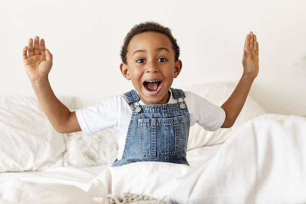 Emotional cute little african american boy sitting on white bed