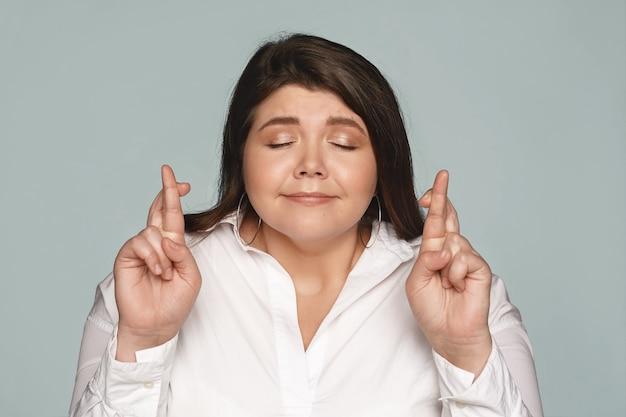 きちんとした感情的なかわいい若いプラスサイズの女性は、目を閉じて指を交差させ続け、大成功した会社での地位を獲得することを熱望しています。幸運を祈る魅力的なぽっちゃり女性