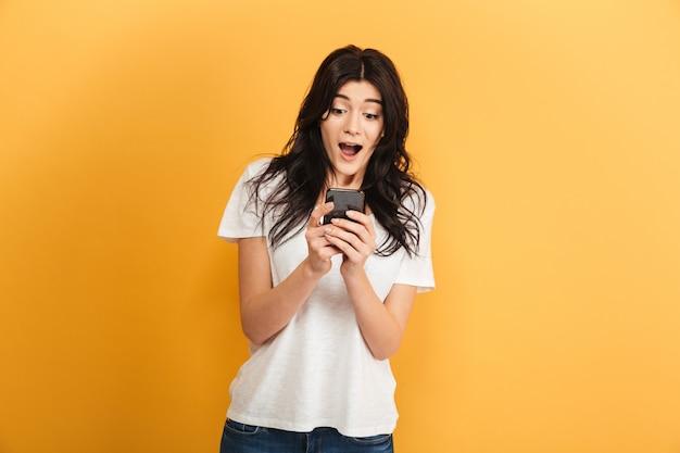 Эмоциональная милая молодая красивая женщина с помощью мобильного телефона, глядя в сторону.