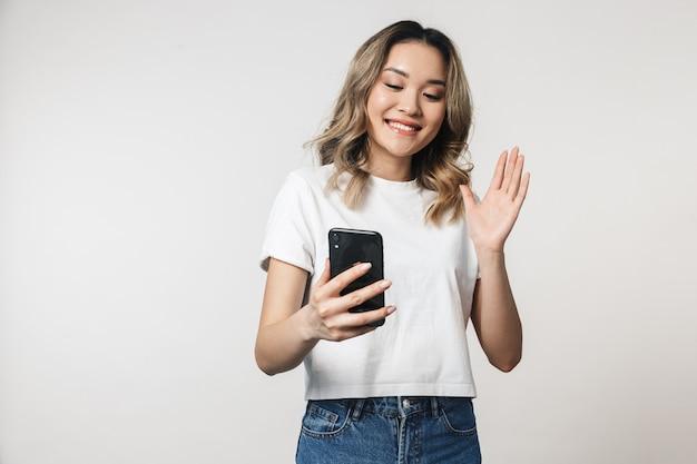 手を振って携帯電話で話している白い壁の壁の上の孤立したポーズの感情的なかわいい若い女性