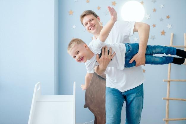 정서적 아빠는 아들을 기르고 밝은 어린이 방에서 비행기가 날고 있음을 묘사합니다.