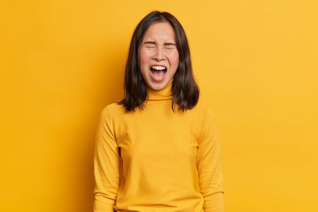 感情的な黒髪のアジア人女性が大声で叫び、怒りを表現し、口を大きく開いたまま、スタジオの背景とワントーンでカジュアルな黄色のタートルネックを着用します。人間の感情と感情の概念