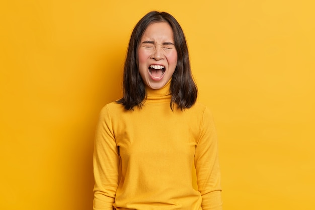 Emotional dark haired asian woman screams loudly expresses rage keeps mouth widely opened wears casual yellow turtleneck in one tone with studio background. human emotions and feelings concept