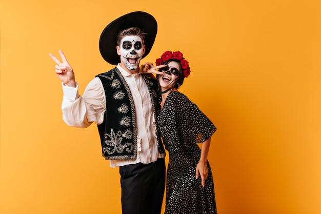 감정적 인 검은 머리 소년과 그의 여자 친구는 평화 기호를 보여주는 멕시코 옷을 입고 재미 있습니다.