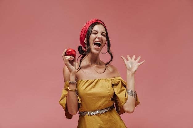 Эмоциональная темноволосая дама со стильными аксессуарами и ярким летним платьем держит красное яблоко и кричит на розовой стене