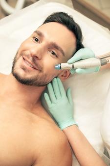 Эмоциональный темноволосый мужчина улыбается, пока косметолог в резиновых перчатках касается его лица во время процедуры питания